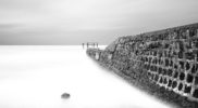 A long exposure, black and white shot of the Old Quay at Walton On The Naze