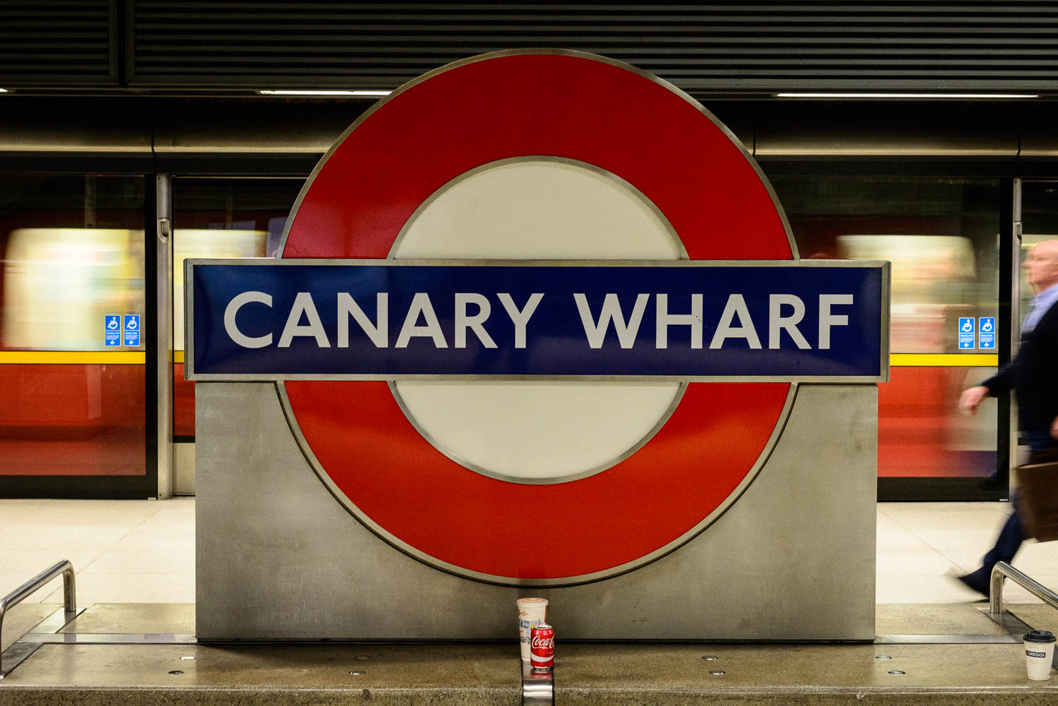 Canary Wharf underground tube sign and rushing tube train and commuter